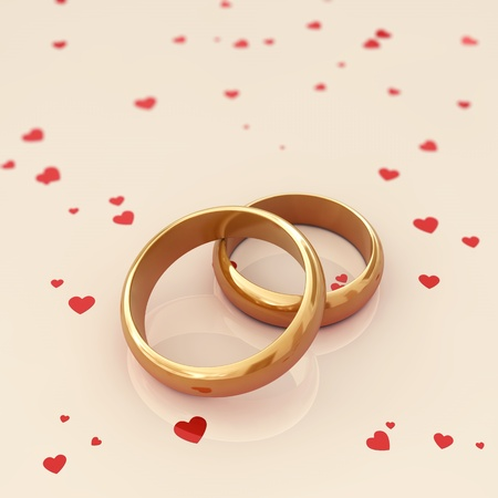 Golden wedding rings on beige background with red hearts photo