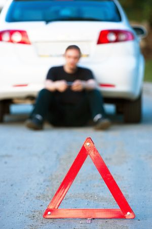 Car accident on a road. Focus is on the red triangle sign photo