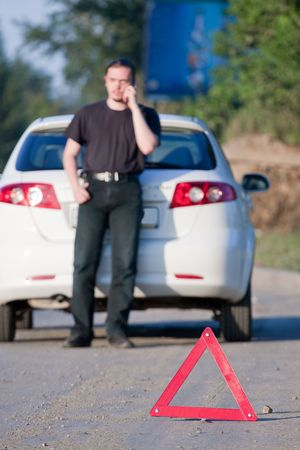 Young man calls to a service standing by a white car. Focus is on the red triangle sign photo
