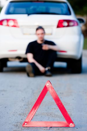 Young man sends an sms sitting by a white car. Focus is on the red triangle sign photo