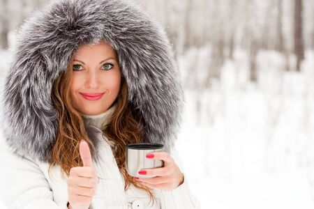 A beautiful caucasian girl drinking hot coffee photo