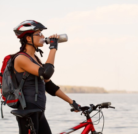 bicycle helmet: Young woman wearing bicycle helmet,standing by bicycle, drinking water from a bottle.  Stock Photo