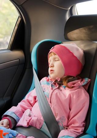Cute little caucasian girl sleeping in a car. photo