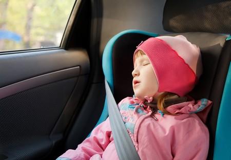 Little caucasian girl sleeping in a car. photo