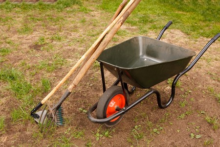 Wheelbarrow and some gardening equipment in a garden. photo