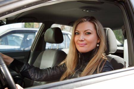 Pretty young caucasian woman in a white car. photo