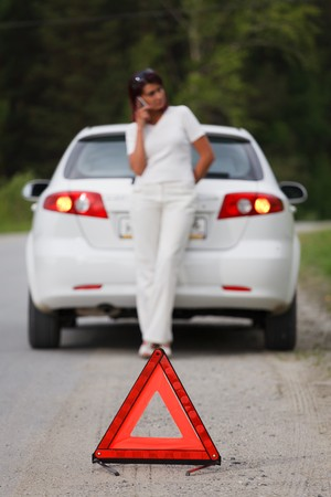 Woman calls to a service standing by a white car. Focus is on the red triangle sign  photo