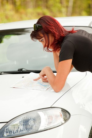 Beautiful Adult Woman Looking At A Map On The Hood Of Her Car. photo