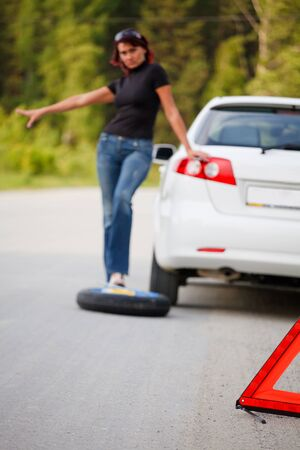 Woman trying to catch someone who may help her. Focus is intentionally located on the red triangle sign. photo