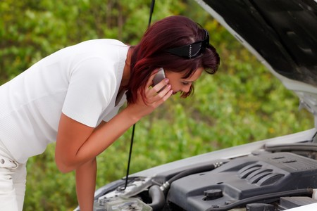 Adult caucasian woman in her car breaks down. Engine failure. photo