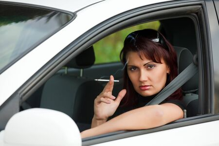 smoking girl: Pretty adult woman sitting in a car and smoking a cigarette Stock Photo
