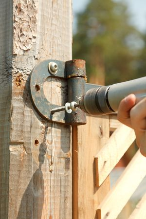 Closeup of contractors hands as he uses a drill to install screws.  Stock Photo - 7172674