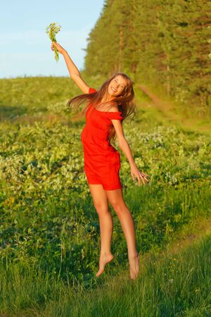 Jumping pretty brunette girl against summer meadow and forest. photo