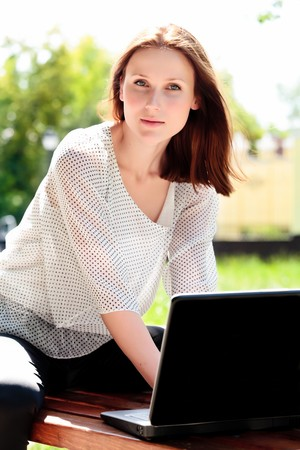Pretty young woman with a laptop at park photo