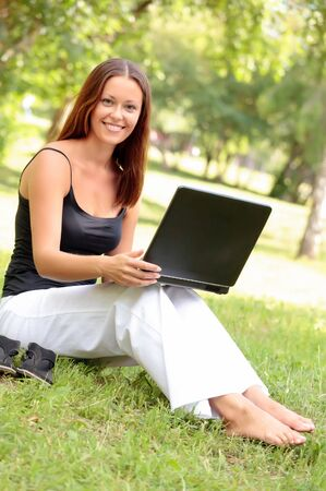 woman barefoot: Beautiful young woman sits on a grass in a park with the laptop. Stock Photo