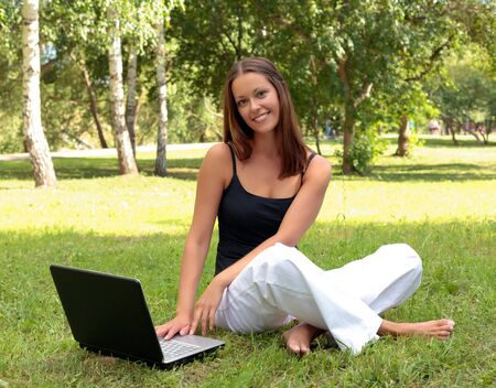 Beautiful young woman sits on a grass in a park with the laptop. photo