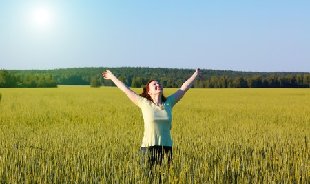 woman with open arms in the green cereal field. photo