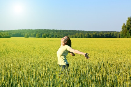 open girl: woman with open arms in the green cereal field.