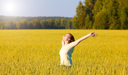 woman with open arms in the cereal field.