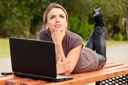 Young pretty woman with laptop lying on the bench in a park Stock Photo - 7347886
