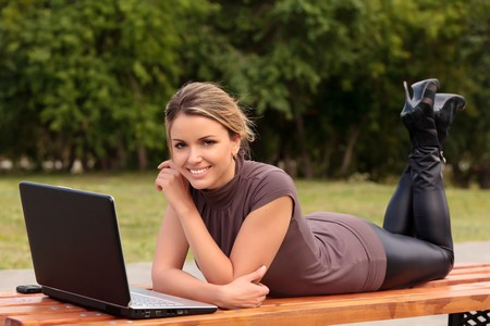 Young pretty woman with laptop lying on the bench in a park Stock Photo - 7347885