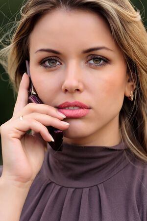 Closeup portrait of a cute young girl talking on mobile phone  photo