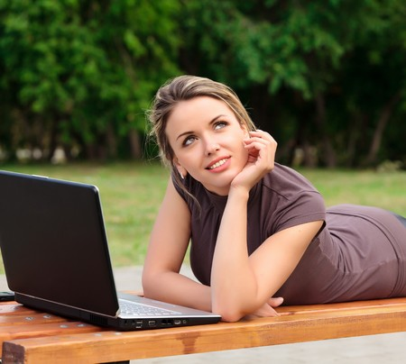 Young pretty woman with laptop lying on the bench in a park Stock Photo - 7360249