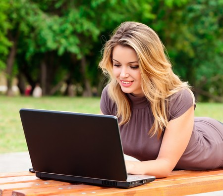 Young pretty woman with laptop lying on the bench in a park photo