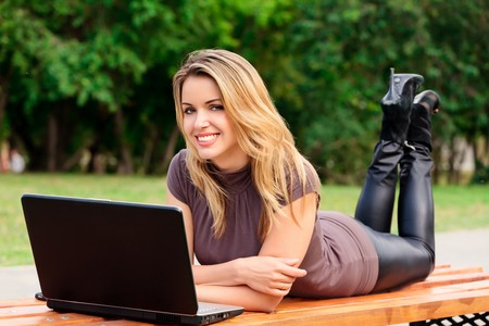 Young pretty woman with laptop lying on the bench in a park Stock Photo - 7360242
