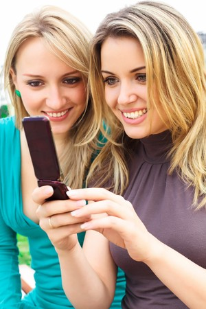 Two smiling girls watching something in mobile phone Stock Photo - 7633249