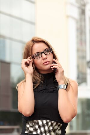 woman wearing glasses: beautiful  young businesswoman talking by mobile phone