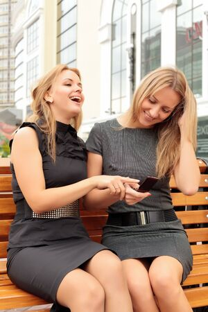 Two smiling girls watching something in mobile phone photo
