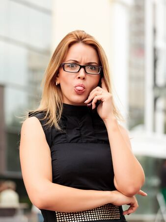 beautiful young businesswoman talking by mobile phone and showing her tongue photo