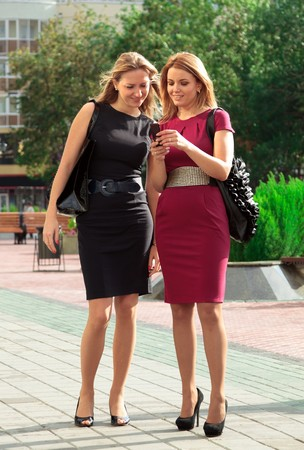 Two young girls are looking on mobile telephone.  photo