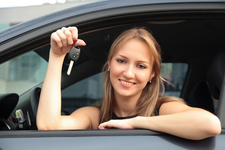 happy woman showing key of her new car photo