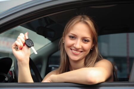 The happy woman showing the key of her new car photo