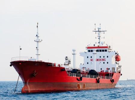 barco petrolero: Petrolero rojo es anclado cerca del puerto.