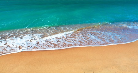 summertime: Sandy beach of seaside resort with clear water. Stock Photo