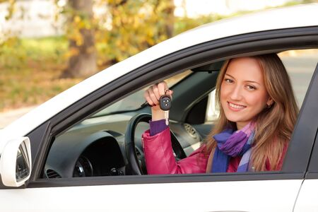 The happy woman showing the key of her new car. photo