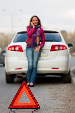 Woman calls to a service standing by a white car. Focus is on the red triangle sign. Evening light. Stock Photo