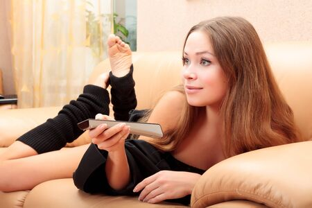 woman laying: Young woman laying on a sofa with remote control and watching tv
