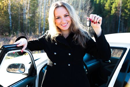 Happy owner of a new car showing a key. photo
