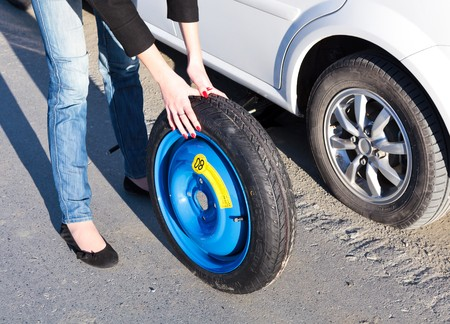 roadside assistance: Woman changing the wheel