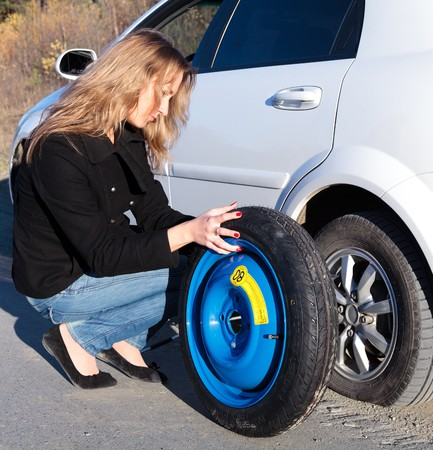 flat tyre: Woman changing the wheel