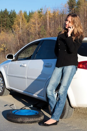 Young woman standing by her damaged car and calling for help photo