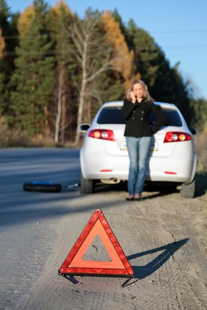 Young woman standing by her damaged car and calling for help. Focus is on the red triangle sign. Shallow depth of view. photo