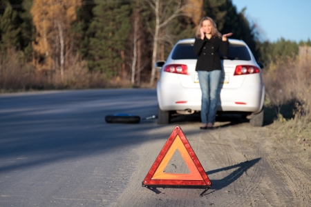 roadside assistance: Young woman standing by her damaged car and calling for help. Focus is on the red triangle sign. Shallow depth of view Stock Photo