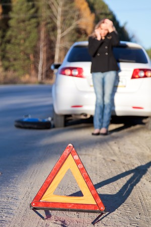 Young woman standing by her damaged car and calling for help. Focus is on the red triangle sign.