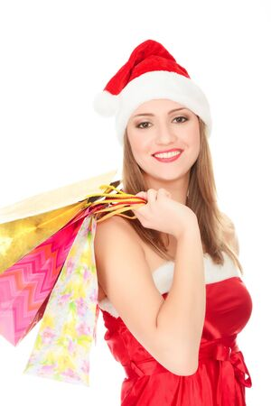 Pretty girl in a red Christmas hat with colorful bags isolated over white
