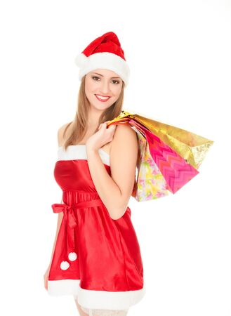 Pretty girl in a red Christmas hat with colorful bags isolated over white background. Stock Photo - 8366946